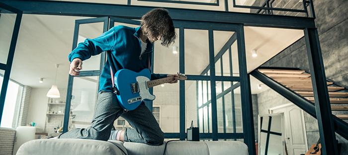 apprendre-la-guitare-seul-en-ligne-homme-canape
